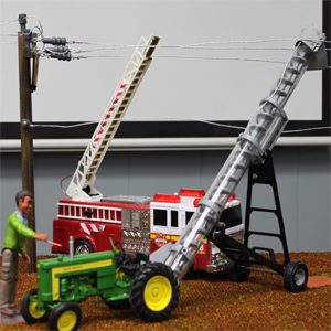 A Plastic Model Touches an Electrically Charged Tractor